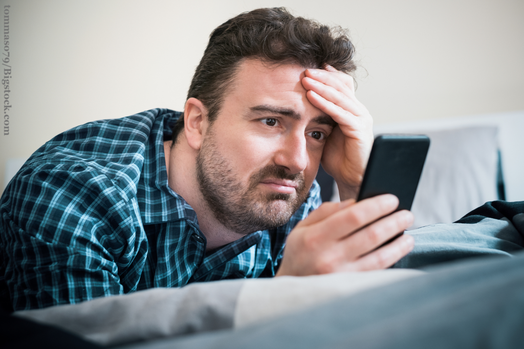 Man using mobile phone in bed at home writing non-stop messages to his date. Avoid dating an obsessed guy.