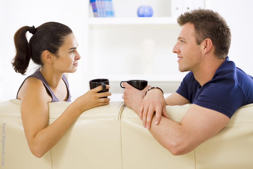 After Dating for months a couple sitting on sofa at home drinking coffee, talking, smiling. Good communication got developed.