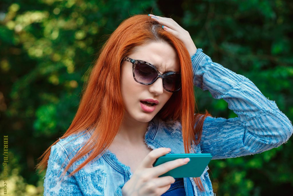 Bad news. Closeup young unhappy frustrated disappointed shocked red head woman girl lady hand on head looking at texting talking on mobile cell phone isolated outdoor green park background Negative face expression