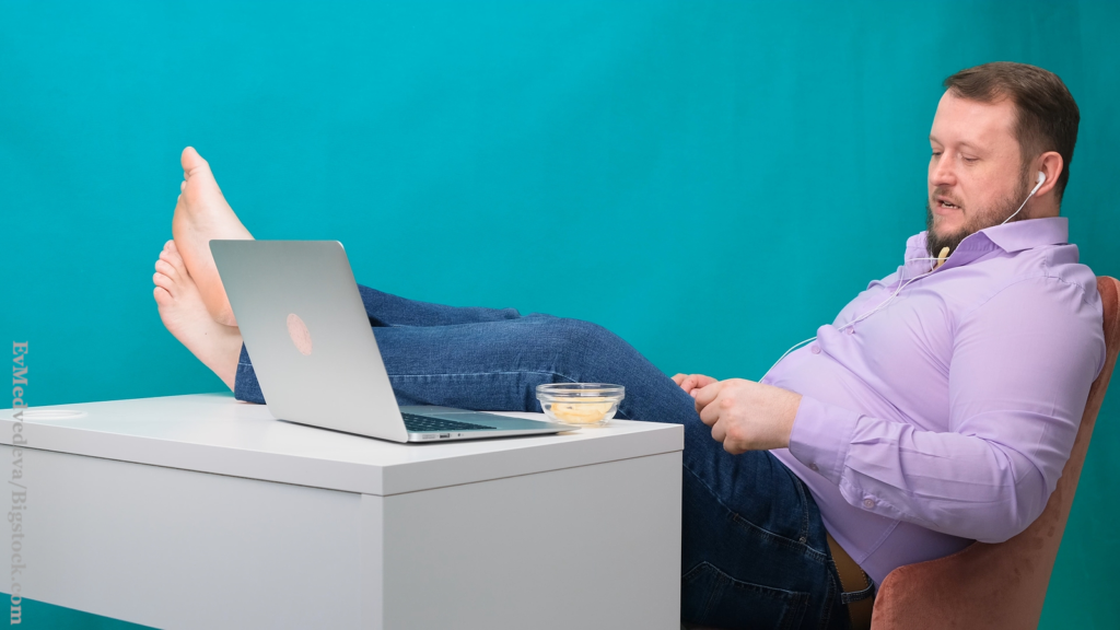 A hidden dating warning sign: A man is being lazy at the workplace with legs on the table eating chips.