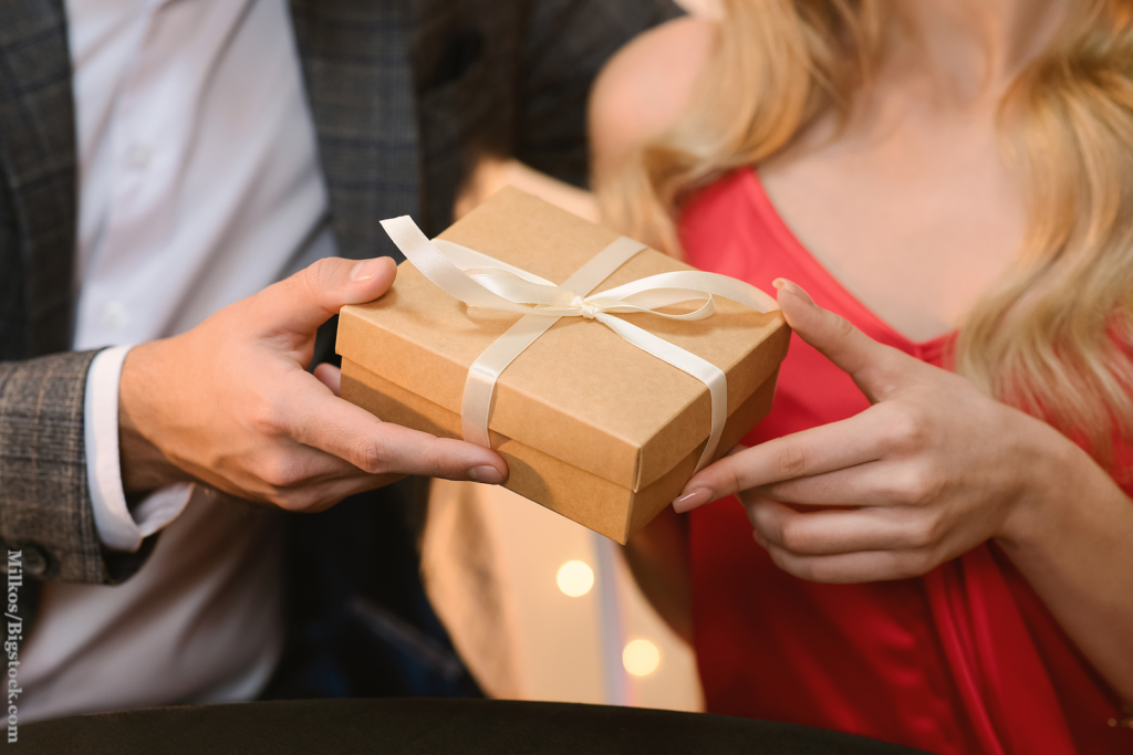 A courting couple: Closeup Of Unrecognizable Man Giving Present Box To His Beloved Woman