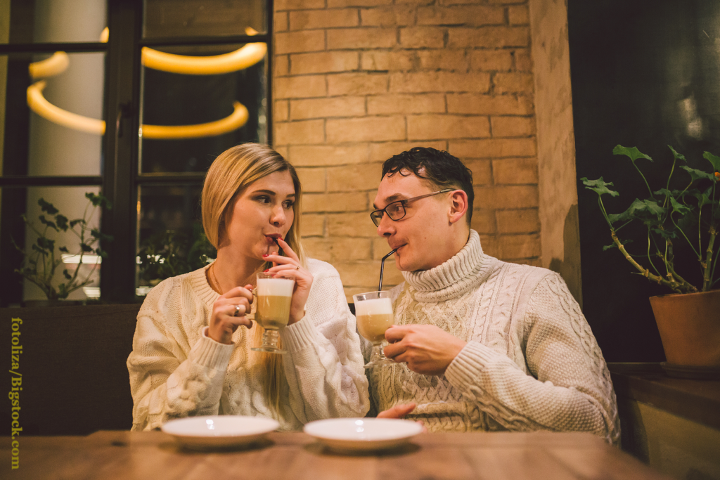 Happy Couple Dating And Drinking Coffee. love and romantic date in downtown cafe restaurant. Young happy couple in love in cafe.