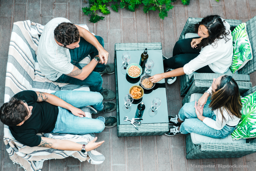 High angle of four friends sitting together on terrace, drinking wine, eating snacks and chatting. Young men and women in casual meeting outside.