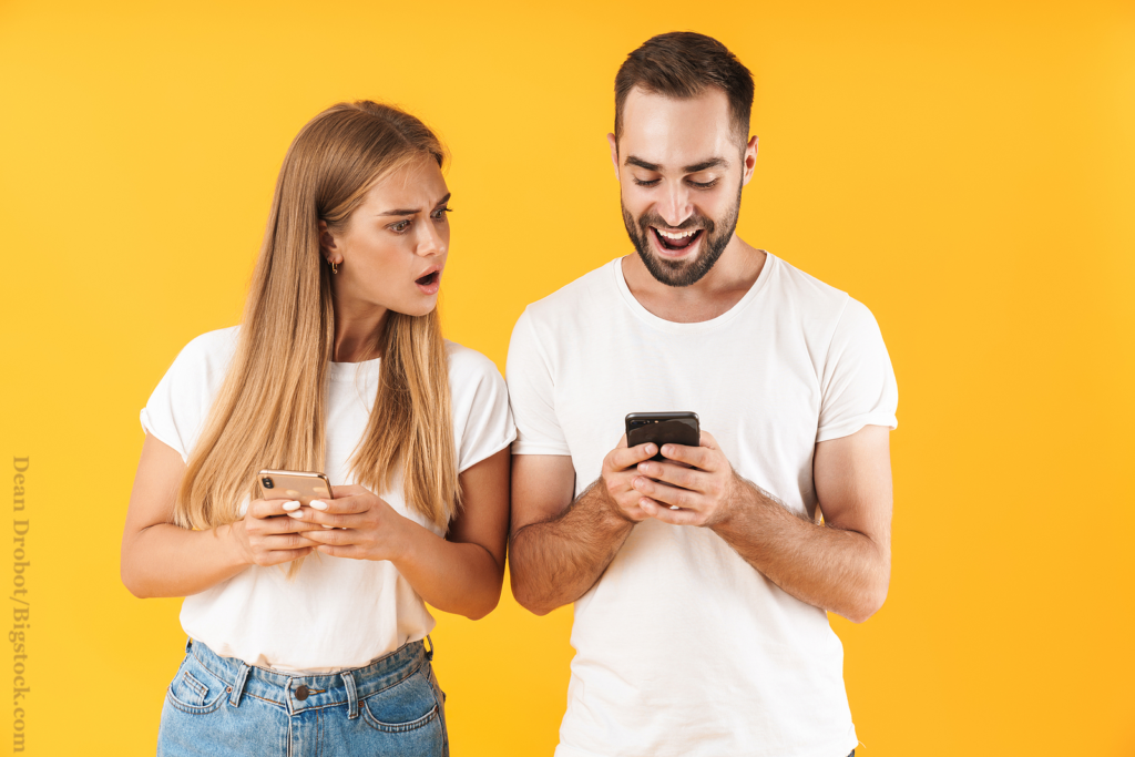 Image of woman spying and peeking at cellphone of her boyfriend isolated over yellow background