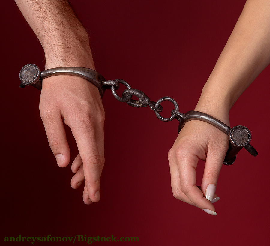Symbolizing a karmic relationship : A man and a woman are hundcuffed together.