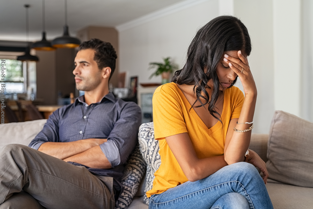 Couple sitting on couch after a fight. Sad woman sitting with hand on head after quarrel with boyfriend at home. Angry couple ignoring each other, relationship troubles.