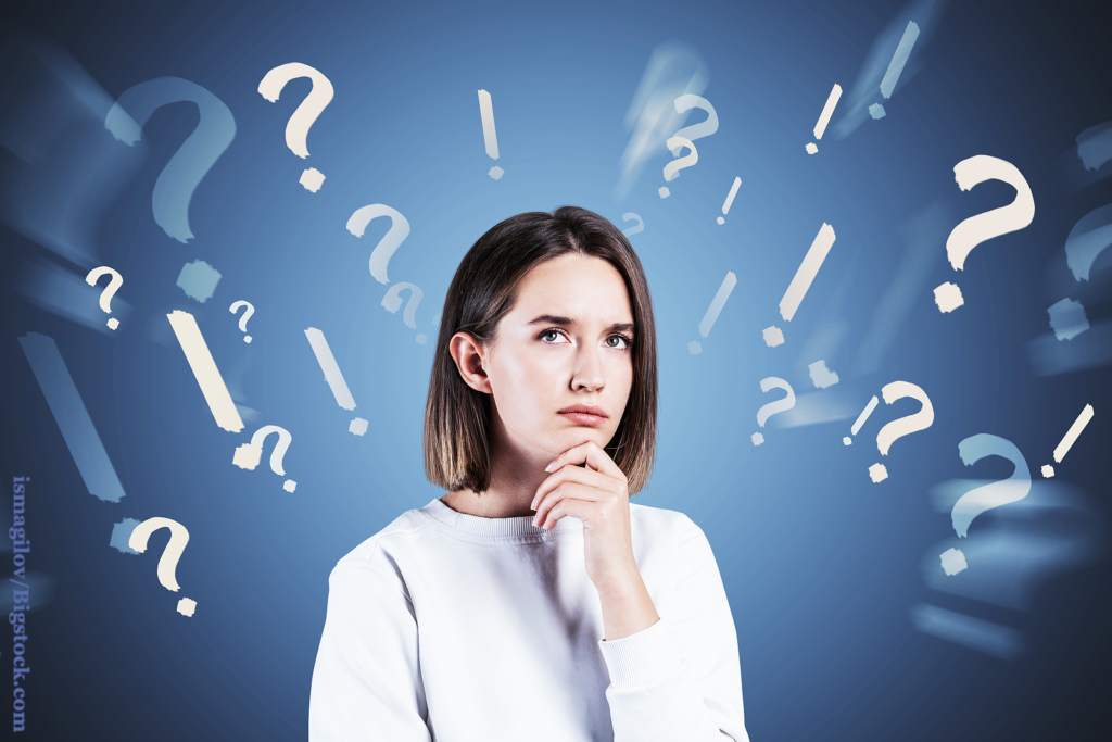 Pensive young woman with short fair hair in casual clothes standing near blue wall with blurry question and exclamation marks. Thinking about the Pros and Cons of Dating and Courting.