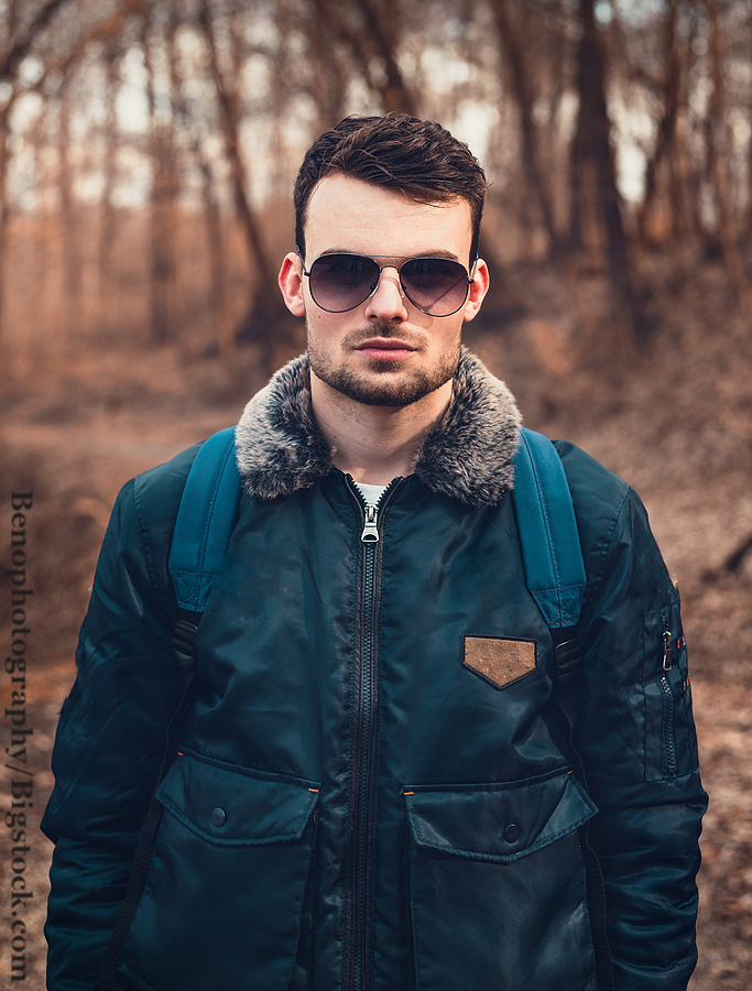 Portrait of young trendy man in blue aviator bomber jacket with sun glasses standing on the path in forest.