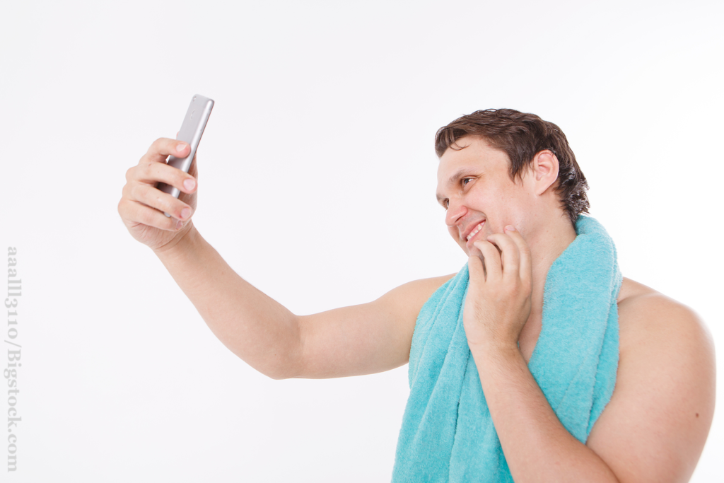 The guy takes a selfie after morning procedures. A man looks at the phone camera. Smooth-shaven face. Blue towel around her neck.