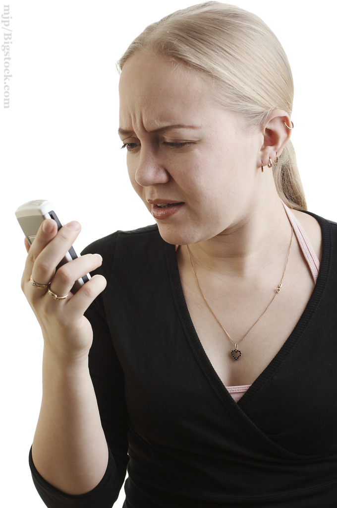 Woman reading text messages on mobile phone