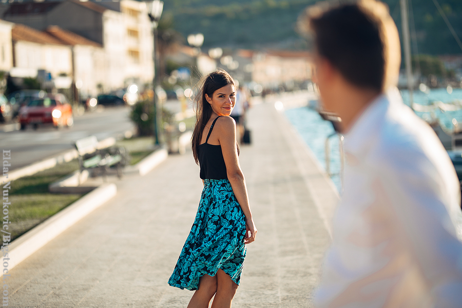 Twin flame attraction: Young attractive woman flirting with a man on the street.Flirty smiling woman looking back on a handsome man.Love at first sight.