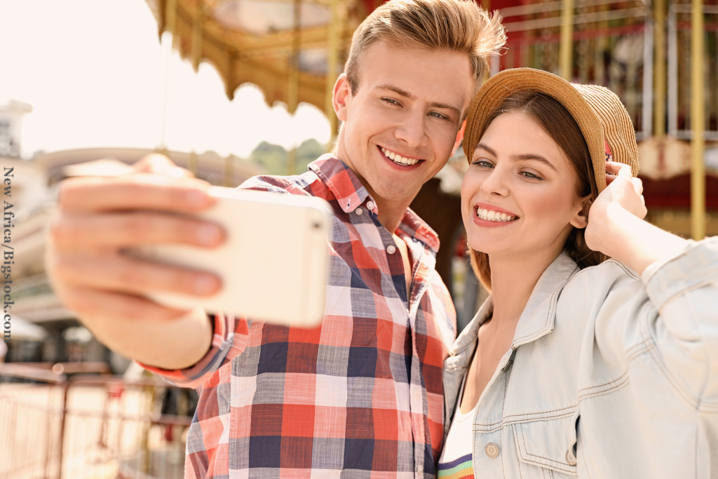 Young happy courting couple taking selfie near carousel in amusement park.