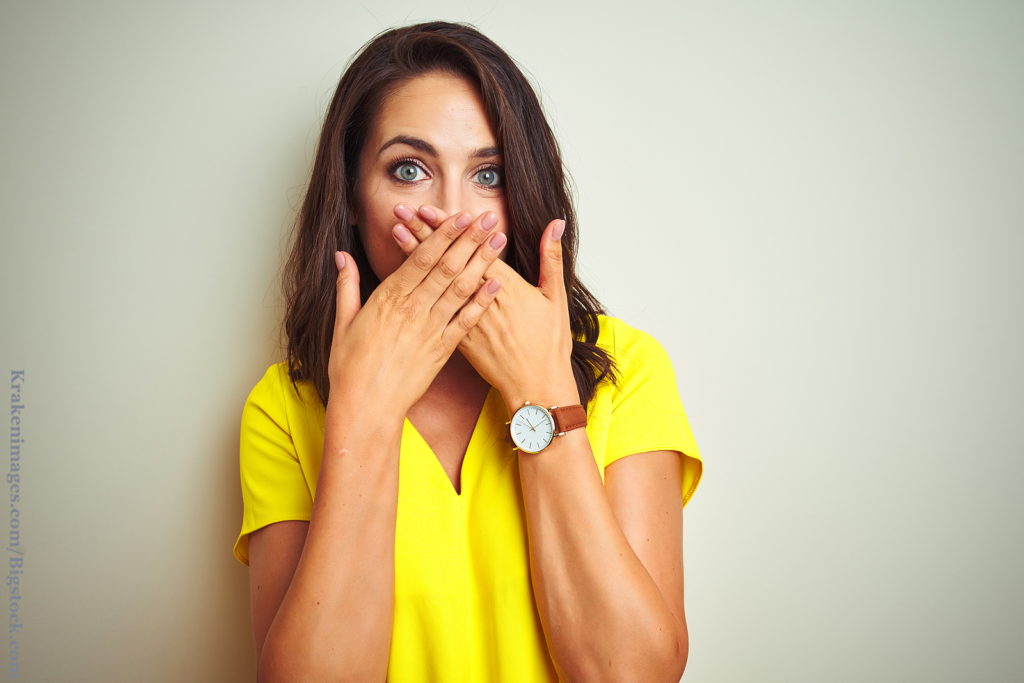 Bad dating karma: Young beautiful woman wearing yellow t-shirt standing over white isolated background shocked covering mouth with hands for being caught in a lie.