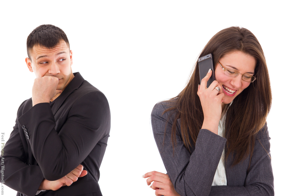 Bad Dating Karma through ignoring your date: suspicious man looking at his woman talking on the phone smiling.