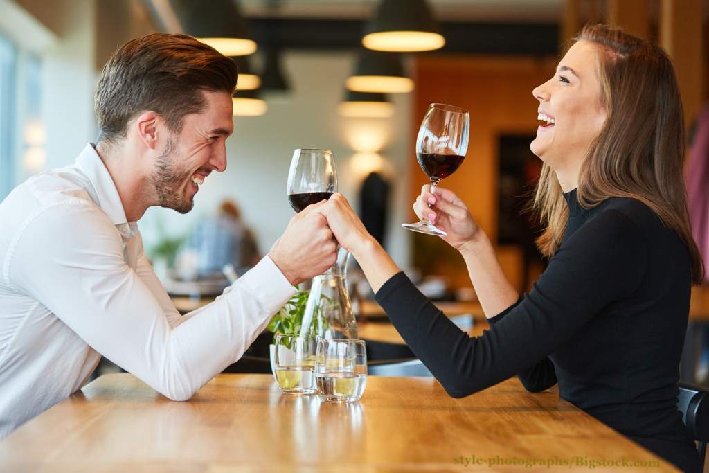 The 3-month rule might be too long. The woman is ready for a relationship. Young man holds hand to laughing woman while dating in restaurant